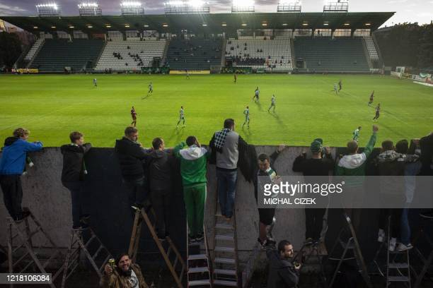 Bohemians' supporters follow the Czech First League football match between Bohemians 1905 and Sparta Praha from behind a wall, amid the new...