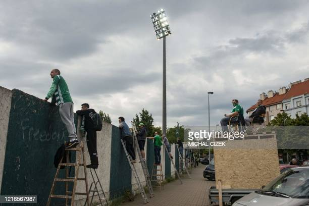 Bohemians' supporters watch the Czech First League football match between Bohemians 1905 and SK Dynamo Ceske Budejovice behind a wall amid the new...