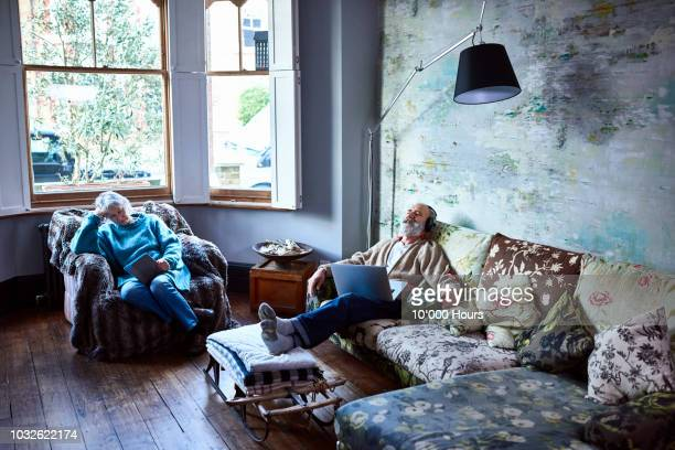 boho couple relaxing at home on sofa with music and ebook - serene people stock pictures, royalty-free photos & images
