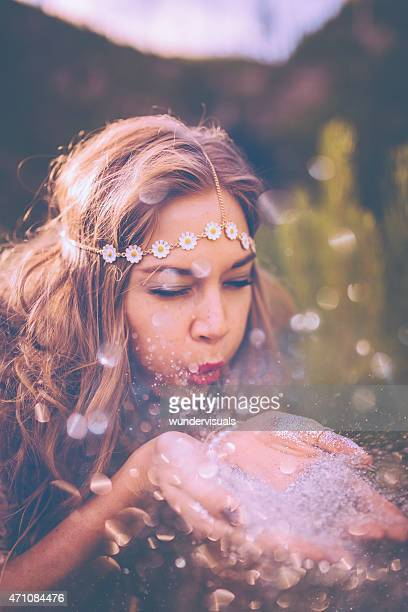 Boho girl blowing silver glitter in nature