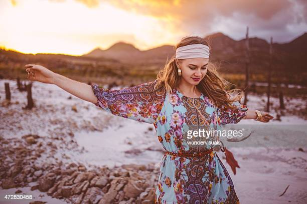 Boho girl dancing in floral dress on a summer evening