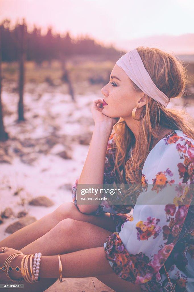 Boho girl in a headband sitting in nature : Stock Photo