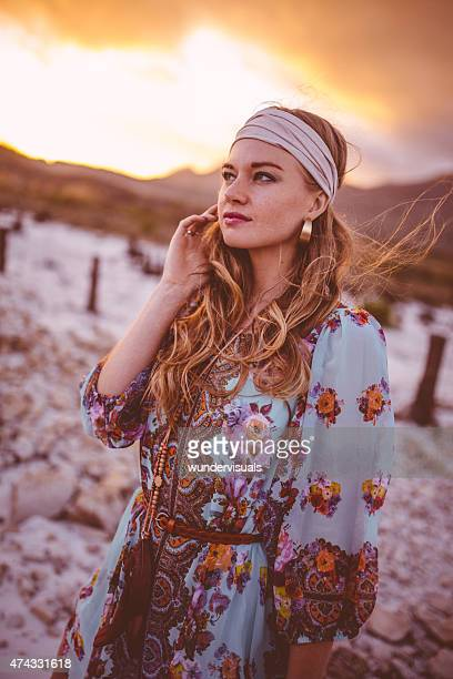 Boho girl in a summer evening landscape with clouds