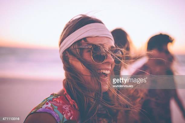 Style bobo fille en lunettes de soleil rire sur la plage avec vos amis