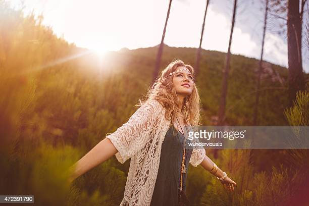 Boho girl in vintage dress in nature with sun flare