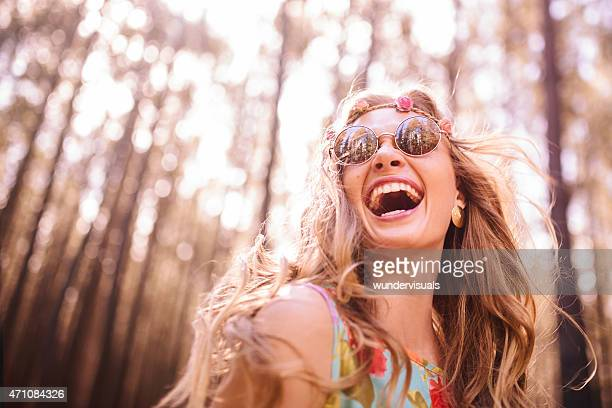 Boho girl laughing in a summer forest