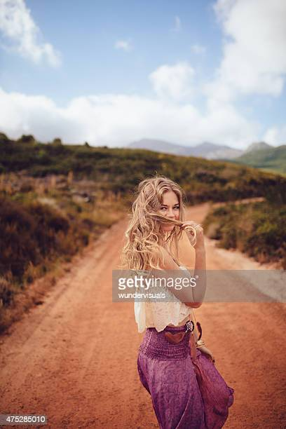 Boho girl looking sweetly at the camera on dirt road