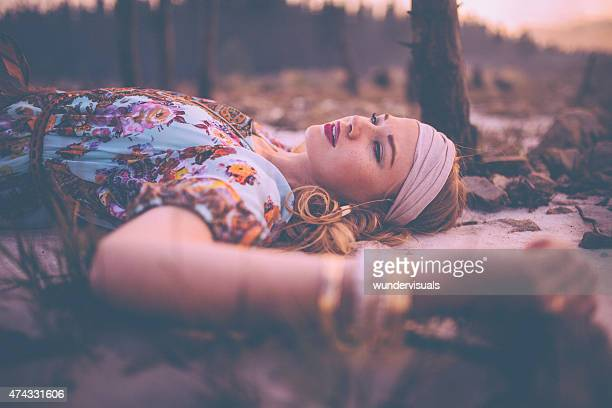 Boho girl lying on the ground in vintage floral dress
