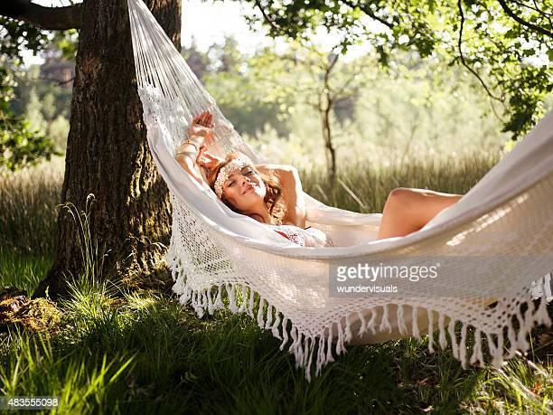 Boho girl relaxing in a vintage white hammock in summer