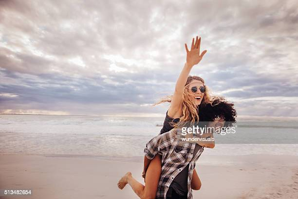 boho girl rides piggyback on hipster man at beach - hippie woman stock photos and pictures