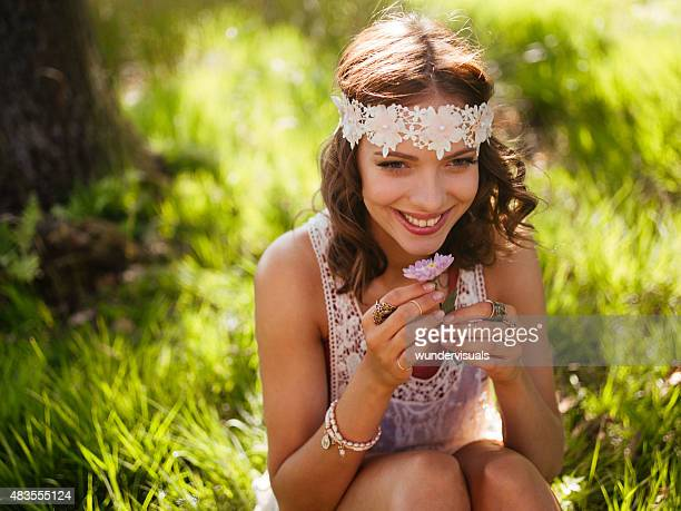 Boho girl smiling and holding a flower in a park