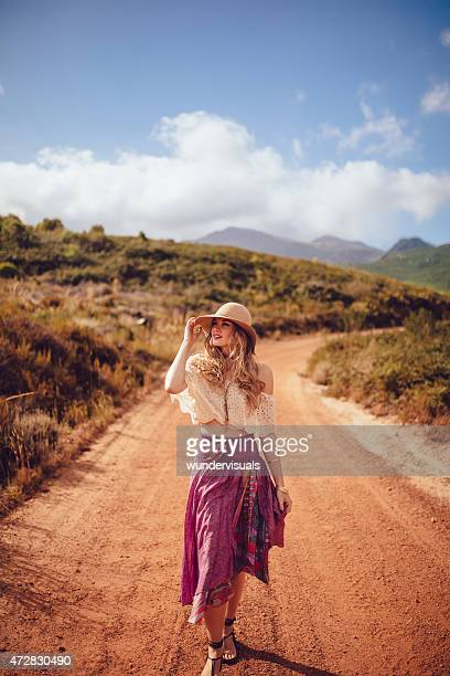 boho girl walking on a dirt road in summer - beige hat stock photos and pictures
