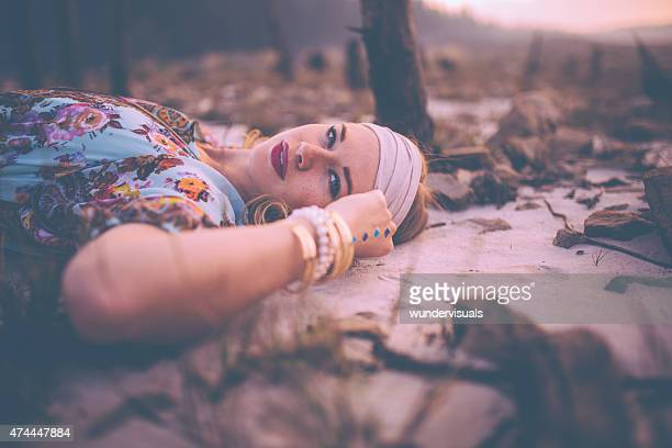 Boho girl with vintage dress and jewellery on sandy ground