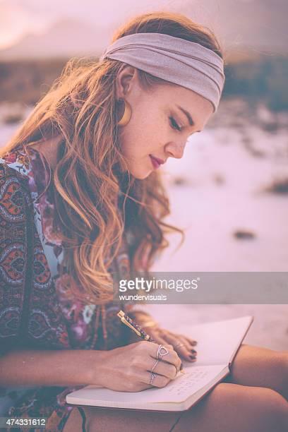 Boho Menina escrevendo no seu diário enquanto surronded por natureza