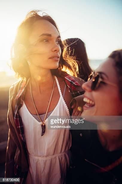 Boho girls having fun at beach with friends