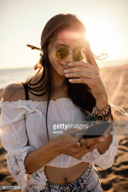 Boho styled woman using her phone on the beach