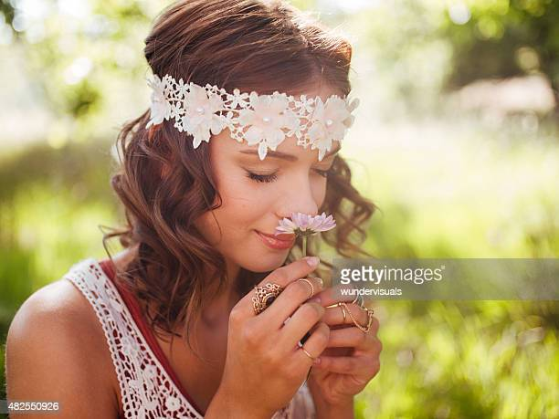 Boho teenager smelling a flower in a summer park