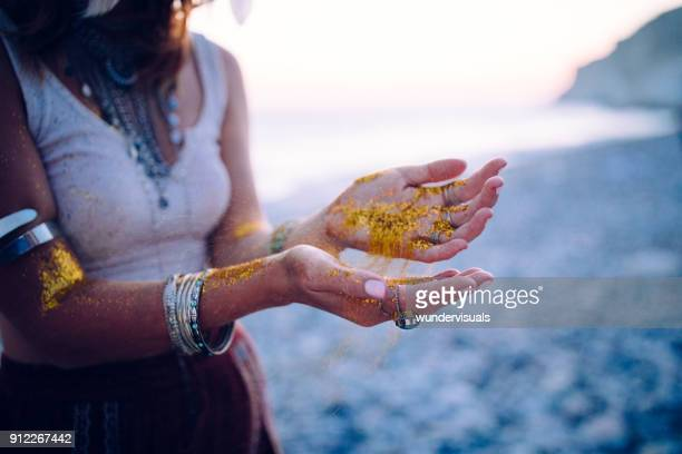 Boho woman at beach with golden glitter on her hands