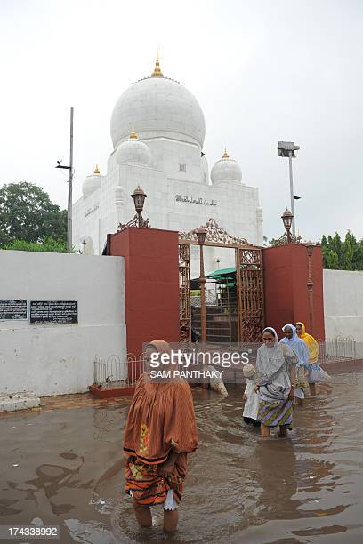 Bohra community members walk through flood waters over the Syedna Qutbuddin Shahid RA Roza street also known as Bohra No Rojo in the Saraspur area of...