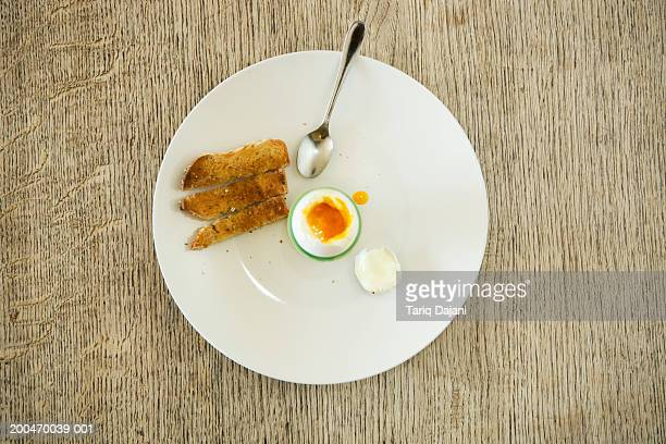 Boiled egg and toast on plate, overhead view