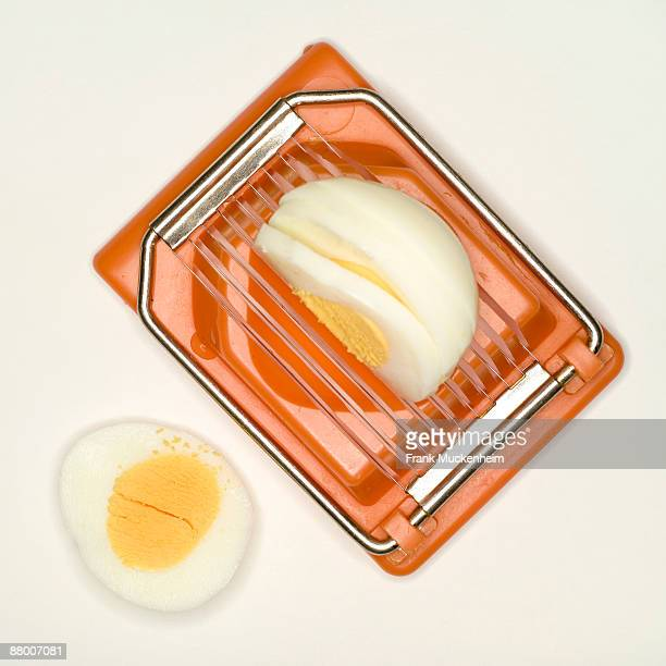 boiled egg in egg slicer, elevated view - hard boiled eggs stock photos and pictures