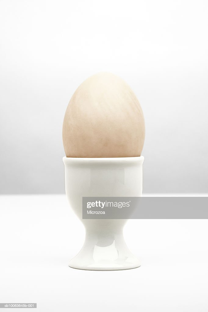 Boiled egg in white egg cup, close-up : Stock Photo