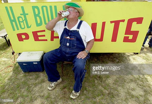 Boiled peanuts chef Ira Johnson has a sip of beer during the 6th annual Summer Redneck Games July 7 2001 in East Dublin Georgia