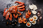 Boiled Seafood on ice - King Crab, Prawn Shrimp, Mussels Clams, Scallops in shells, Octopus mini, Squid on Grill