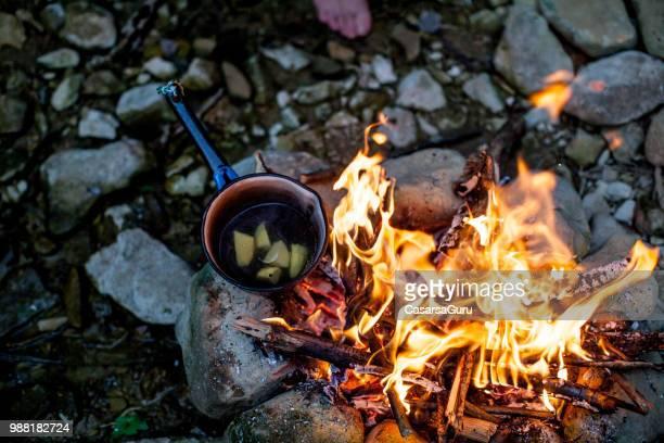 kochende kartoffeln am lagerfeuer - überleben stock-fotos und bilder