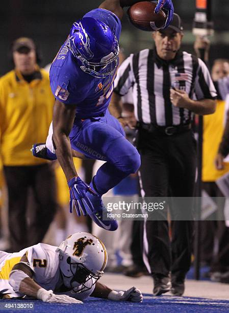 Boise State running back Jeremy McNichols leaps over Wyoming's Robert Priester at Albertsons Stadium in Boise Idaho on Saturday Oct 24 2015