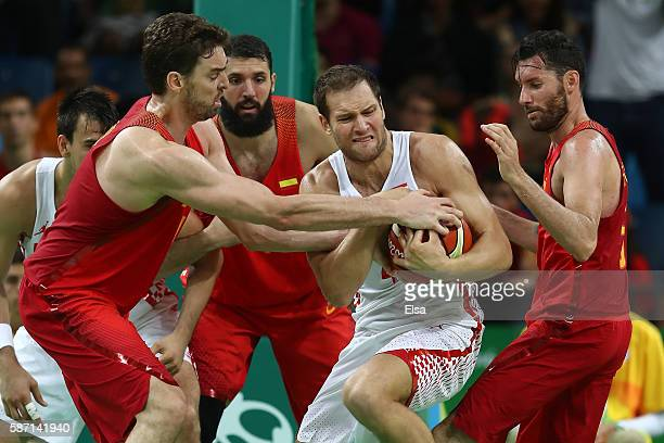 Bojan Bogdanovic of Croatia and Pau Gasol of Spain fight for a rebound during a Men's preliminary round basketball game between Croatia and Spain on...