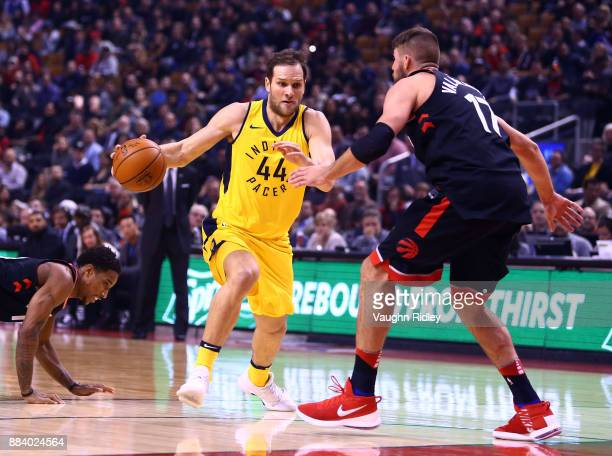 Bojan Bogdanovic of the Indiana Pacers dribbles the ball as Jonas Valanciunas of the Toronto Raptors defends during the first half of an NBA game at...