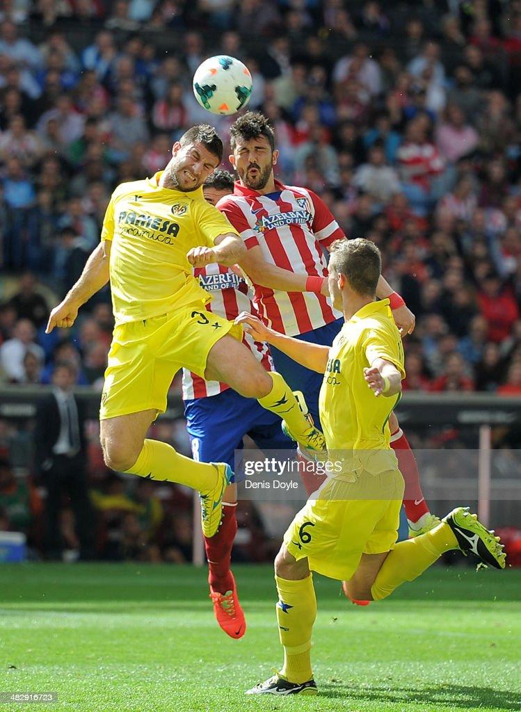Bojan Jokic (L) of Real Villarreal battles for the ball against David Villa of Club Atletico de Madrid during the La Liga match between Club Atletico de Madrid and Real Villarreal at Vicente Calderon stadium on April 5, 2014 in Madrid, Spain.