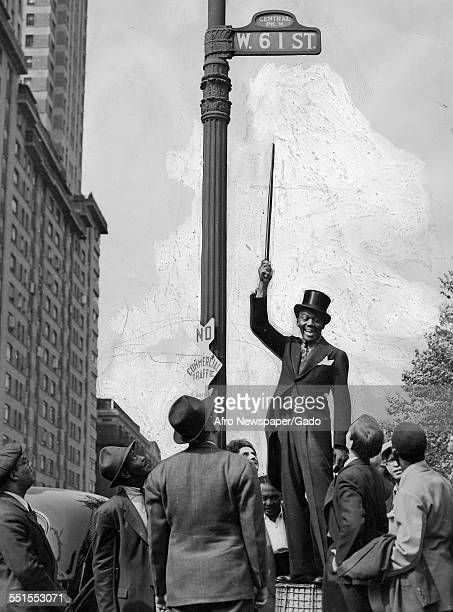 Bojangles in a dinner suit and top hat pointing to the road sign above his head W 61st Street on Broadway on his 61st birthday New York City New York...