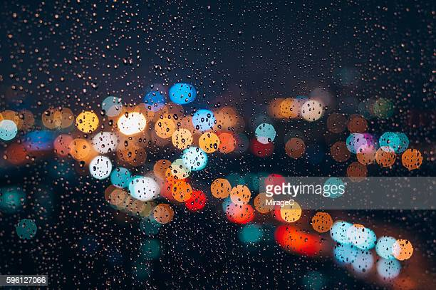 Bokeh of City Behind the Rainy Night Window Glass