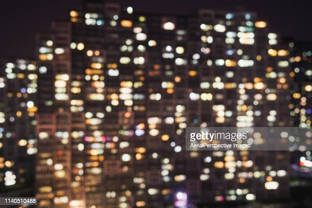 bokeh view of residential building at night - fensterfront stock-fotos und bilder
