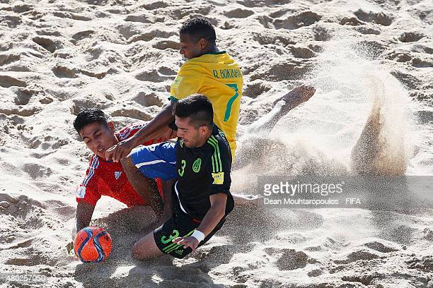 Bokinha of Brazil battles for the ball with Miguel Estrada and Carlos Hernandez of Mexico during the Group C FIFA Beach Soccer World Cup match...