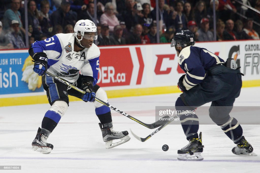 Bokondji Imama #51 of the Saint John Sea Dogs moves the puck against forward Jeremiah Addison #10 of the Windsor Spitfires on May 19, 2017 during Game 1 of the Mastercard Memorial Cup at the WFCU Centre in Windsor, Ontario, Canada.