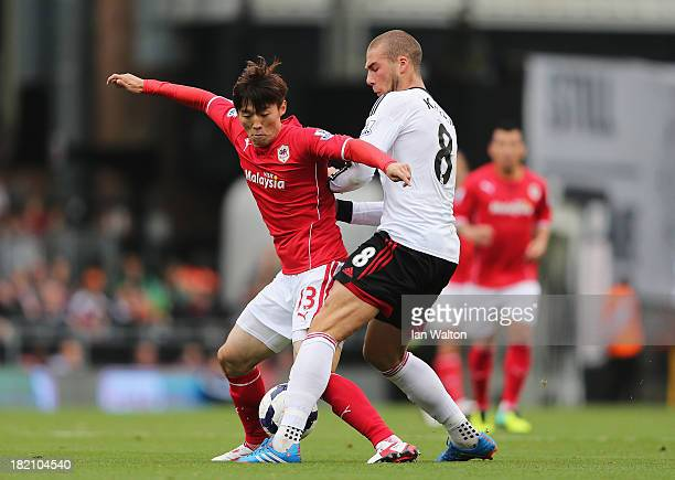 BoKyung Kim of Cardiff City tackles Pajtim Kasami of Fulham during the Barclays Premier League match between Fulham and Cardiff City at Craven...