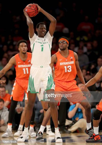 Bol Bol of the Oregon Ducks looks to pass as Oshae Brissett and Paschal Chukwu of the Syracuse Orange defend during the 2K Empire Classic at Madison...