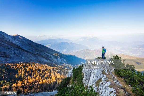 bold - alone rock climber is standing at rock ledge - berchtesgaden stock pictures, royalty-free photos & images