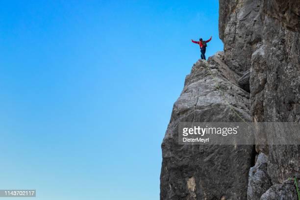 bold-alone rock climber heben arme am felsvorsprung-watzmann - extremlandschaft stock-fotos und bilder