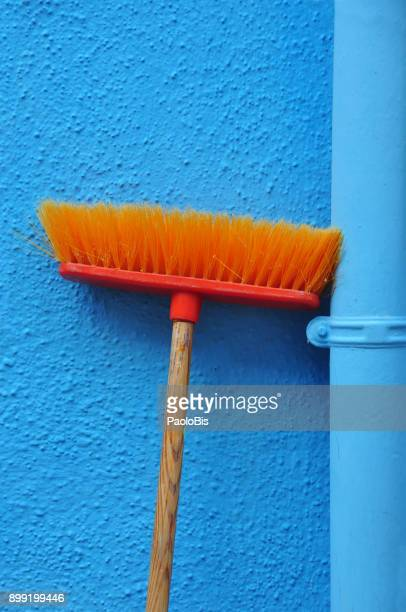 bold colours - orange broom on blue wall, burano, venezia - broom stock pictures, royalty-free photos & images