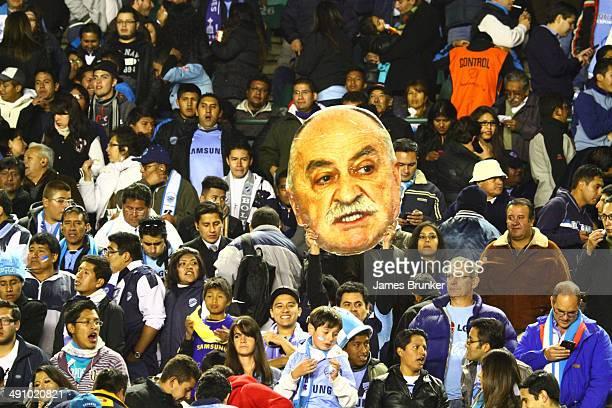 Bolivar fans hold up a giant portrait of their team's coach Xabier Azkargorta during a second leg quarter final match between Bolívar and Lanús as...