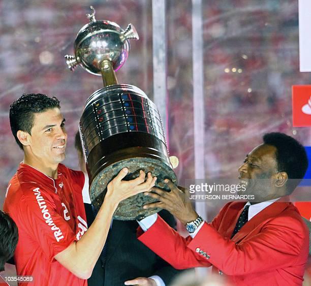 Bolivar of Brazilian Internacional receives the Libertadores Cup from Brazilian football legend Pele at Beira Rio stadium in Porto Alegre Brazil on...