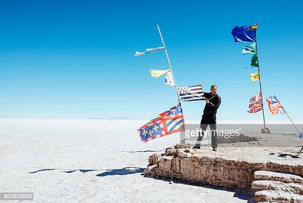 Bolivia, Atacama, Altiplano, Salar de Uyuni, Flags from all countries, man holding a flag