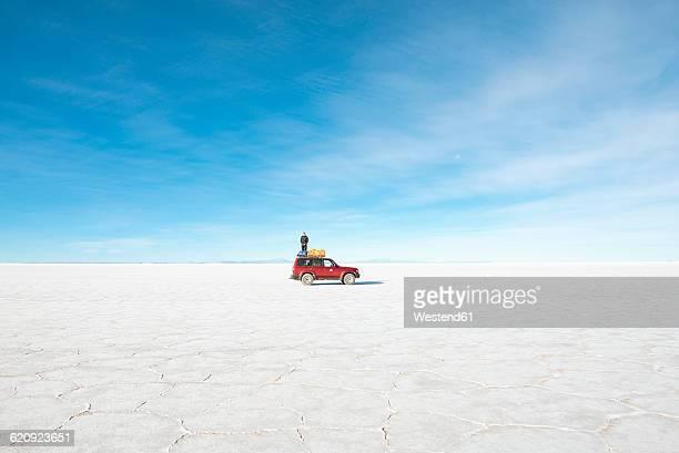 Bolivia, Atacama, Altiplano, Salar de Uyuni, Man standing on a 4x4 car