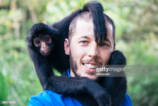 bolivia, coroico, portrait of smiling man with black spider monkey on his shoulders - monkey paw stock photos and pictures