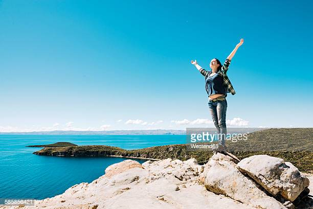 Bolivia, La Paz Department, Happy woman with raised arms on top of Isla del sol on Lake Titicaca