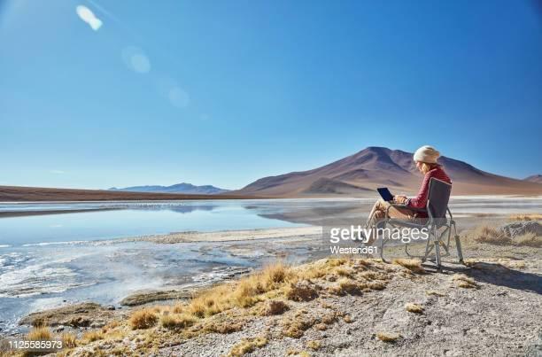 Bolivia, Laguna Colorada, woman sitting on camping chair at lakeshore using tablet